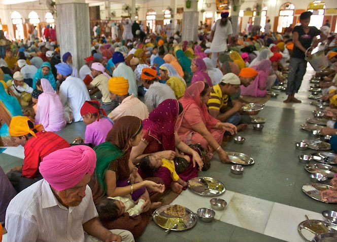 "Langar Seva (Free Kitchen) - The three tenets of Sikhism namely; Naam Japna (meditate on the name of God), Kirat karna (honest living) , and Vand Chakna (sharing with others) are the corner stones for all Sikhs. Out of these, Vand Chakna, sharing with all, has been extended into the institution of Langar, something unique to the Sikhs. Langar means a Sikh communal meal. The first Guru, Guru Nanak started this tradition by feeding the holy hungry men. It was a free meal to be given to all, regardless of their background. Guru Nanak Devji wanted to uphold the principles of equality, regardless of religious background, caste, creed, colour, age, gender or social status. The 3rd Guru, Guru Amar Dass, took it further and made it an institution. Food was to be cooked in a common kitchen and distributed to all sitting on an equal footing, no matter what their background. It is said the great King Akbar had to share the meal with the common people, sitting amongst them. No special privileges were given to him.Langar is usually cooked by volunteers in a common kitchen, with donated ingredients. It is vegetarian so does not encroach on anyone's religious or personal beliefs. Langar is served in all Gurdwaras across the world, as it has become an integral part of their life. Anyone is welcome to partake of the meal. Today it has gone beyond the Gurdwaras. Now volunteers take Langar wherever it is needed, especially to disaster areas or to a community in need. Being vegetarian it is accepted by all. This to show the ""oneness of all humankind"""