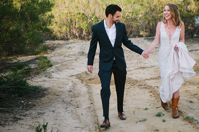Anza-valley-wedding-at-the-alpaca-farm-bride-and-groom-walking-holding-up-dress.jpg