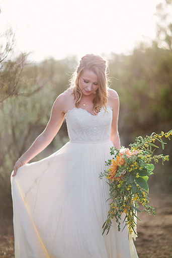 Anza-valley-wedding-at-the-alpaca-farm-bride-holding-dress-with-green-and-yellow-floral-bridal-bouquet.jpg