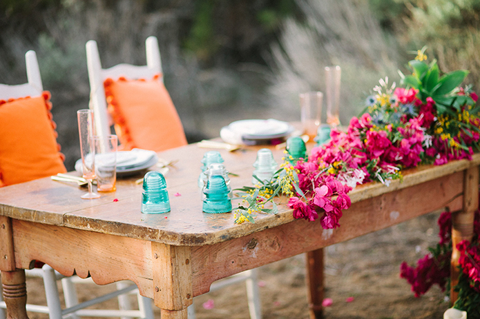 Anza-valley-wedding-at-the-alpaca-farm-brown-wood-table-with-bright-pink-flowers-and-orange-chairs.jpg