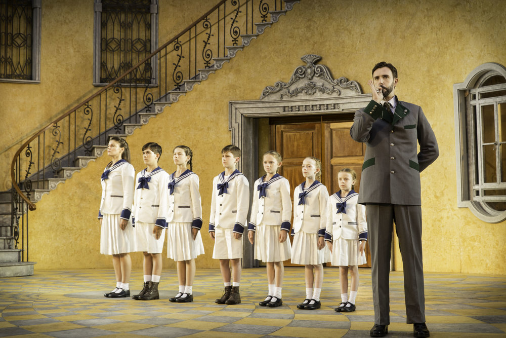 5. Michael Xavier as Captain von Trapp and the children. Photo Johan Persson.jpg