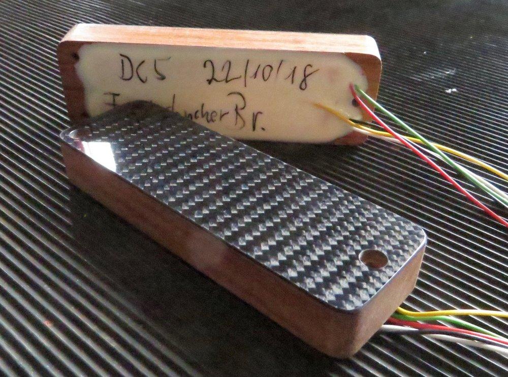 - Da die verwendeten Hyperaktive Tonabnehmer kleiner sind als andere Soapbars, gibt es keine Kunststoffkappen dafür. Also macht Chris auf der Basis unserer Hotwire Funderbucker passende Kappen aus Bubinga, und leimt eine Carbon-Auflage drauf. Sieht gut aus.