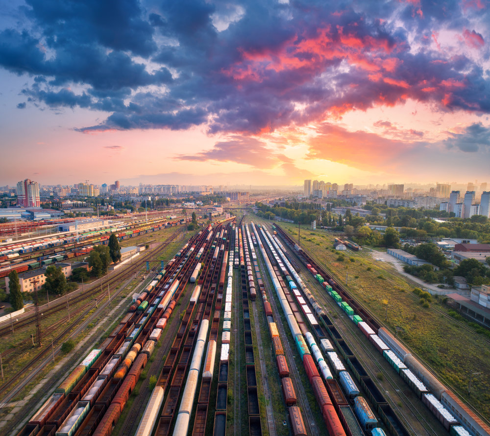 Cargo-trains.-Aerial-view-of-colorful-freight-trains.-Railway-station.-Wagons-with-goods-on-railroad.-Heavy-industry.-Industrial-scene-with-trains,-city-buildings-and-cloudy-sky-at-sunset.-Top-view-827527560_5302x4711.jpeg