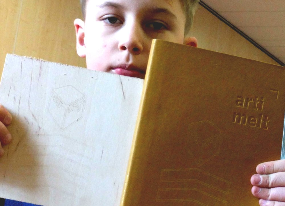KidsCanBUILD: Design Thinking 101 student shows off his personal logo that has been laser etched on wood and leather journal.