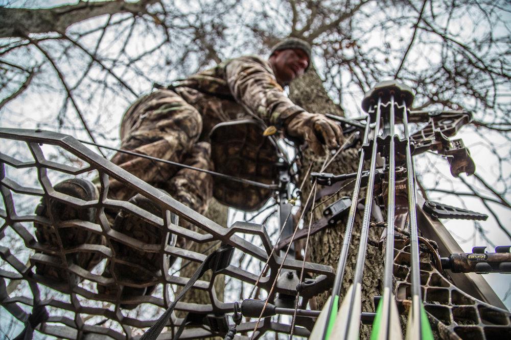 bowhunter-grabbing-bow-in-treestand.jpg