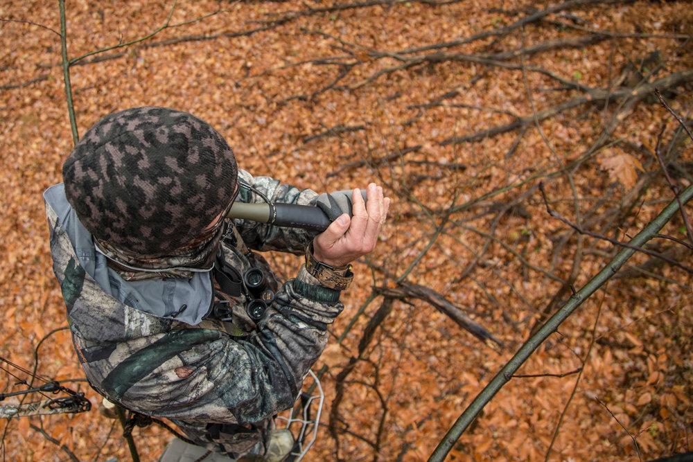 deer-hunter-using-grunt-call-in-treestand.jpg