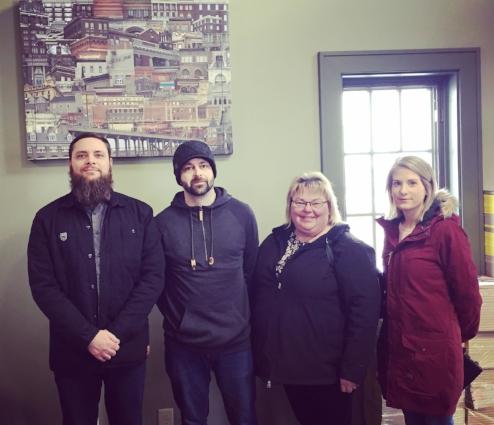 Contest winners posing in front of the freshly unveiled photo collaboration collage project between Tourism Moose Jaw and the Moose Jaw Camera Club.  From left to right: Chad Klyne, Jonathon Charles, Sandra Frey and Shayna Kennedy. (Not pictured - Megan Keller and Krystal Moore)