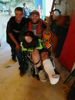 Travis Geib, bassist for Johnny 2 Fingers & the Deformities, nursing the ankle he broke preparing for Band City Fest. Beside him is Michael, the event's Teflon vested security guard.