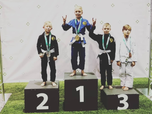 Roque Spaan-Murray accepting one of his two Gold Medals. Here he is, on the podium, flanked by two of his teammates, Dominic Myers on the left and Phoenix Kivol on the right. In the white Gi is Oliver Moellenbeck from Diekema Martial Arts in Saskatoon