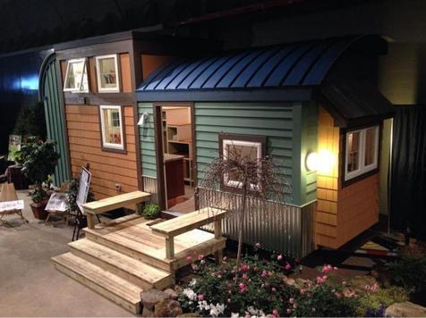 "The exterior of the tiny home in ""The Tiny Village"", that also housed two shipping container spaces. The tiny home actually has an owner, and I worked with her to select fun and funky exterior colors and lighting fixtures to reflect her style."