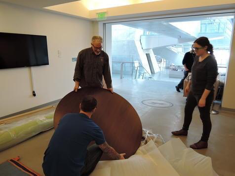 John Strauss and museum crew unwrapping the dining table top.