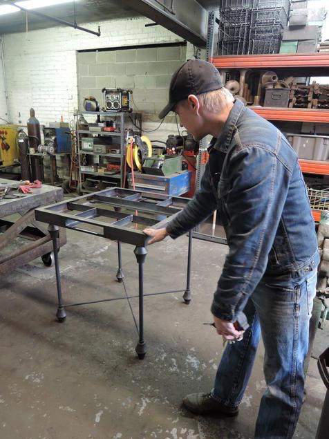 Kevin Busta showing me the progression of the game table he is making for the exhibition