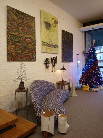 """The three large paintings on the brick wall are by John Sokol. Small side tables by Bomb Factory Furniture. Unconventional Christmas trees by Michael Marras and Doug Meyers. Lamp by Damon Drummond.Found object assemblage pieces, """"Mr. and Mrs."""", by Gwen Waight."""