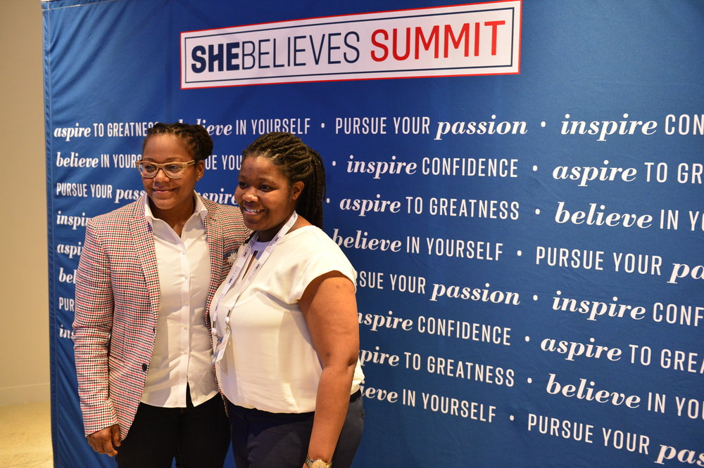 Phaidra Knight takes a photo with a SheBelieves Summit attendee.