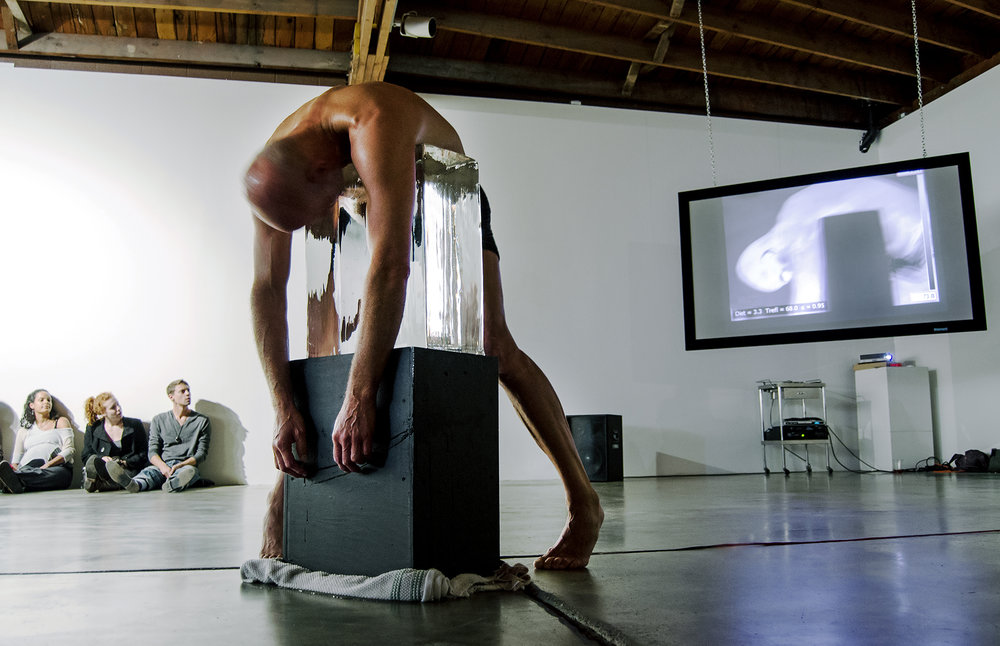 INCIDENT ENERGY - Performance view. Choreographer Jim McGinn dances with a pillar of ice with an infrared live feed on screen. The heating and cooling changes are seen in real time. Performance at Disjecta Contemporary Fine Art, Portland, Oregon. 2013.