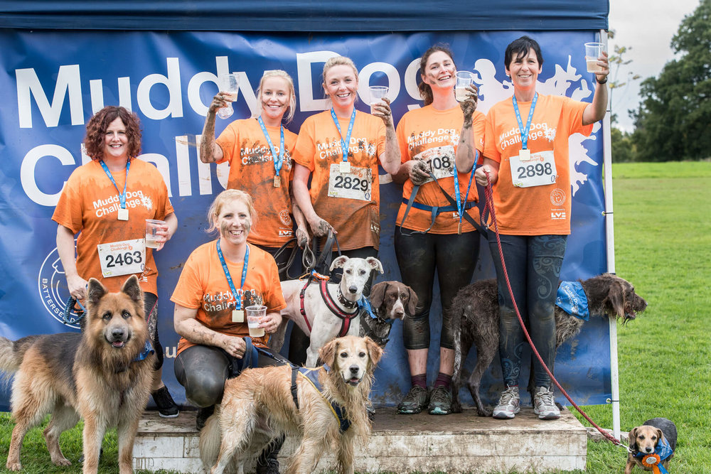 Humans and dogs celebrating at the end of the Muddy Dog Challenge
