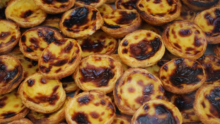 Portugal - Pasteis de Nata are custard tarts with rich, eggy mixtures wobbling inside pastry cups.
