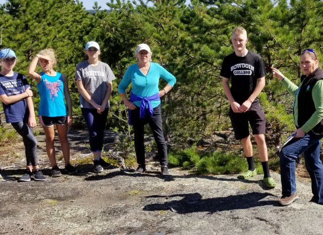 Thomas (in the Bowdoin t-shirt) led a guided hike of the trail and shared how he worked with KELT staff to plan and complete trail construction.