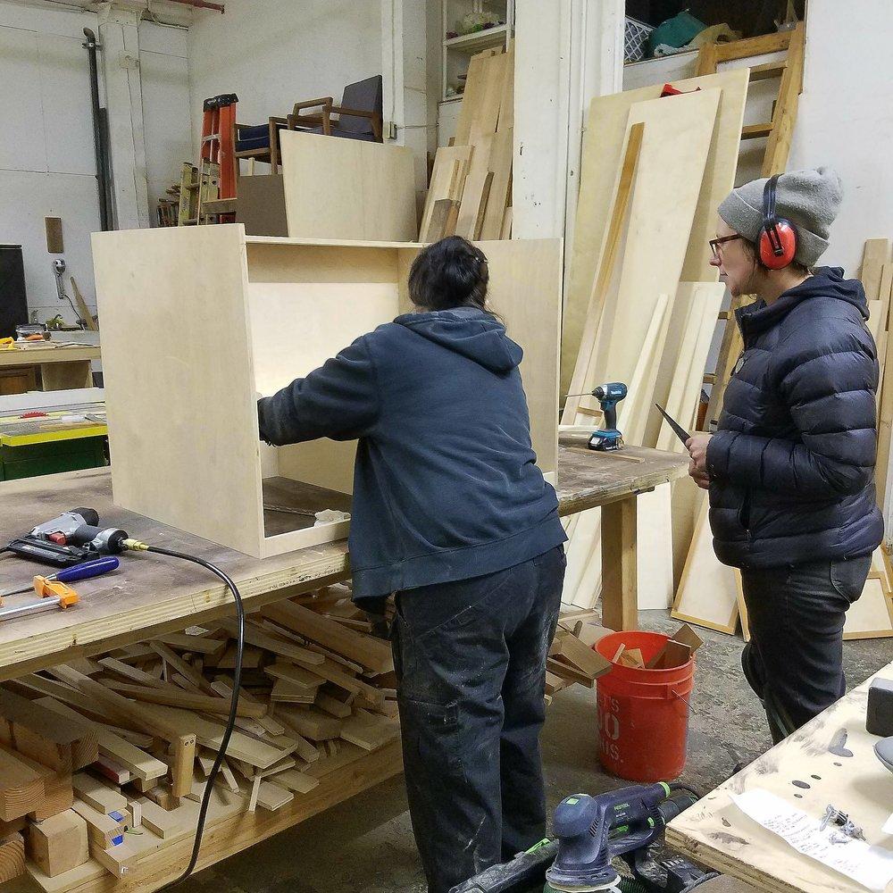 Apprentice Em helps Chisel Core Maker Victoria build a cabinet