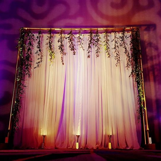 Gold Pipe Backdrop With White Curtains Greenery And Uplighting
