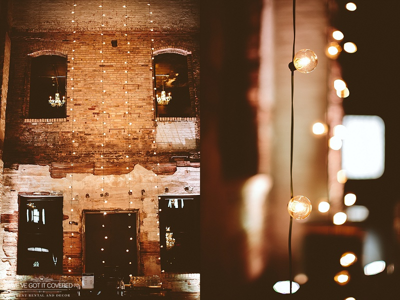 Cafe lights strung down a beautiful brick wall with the accompaniment of a few crystal chandeliers.