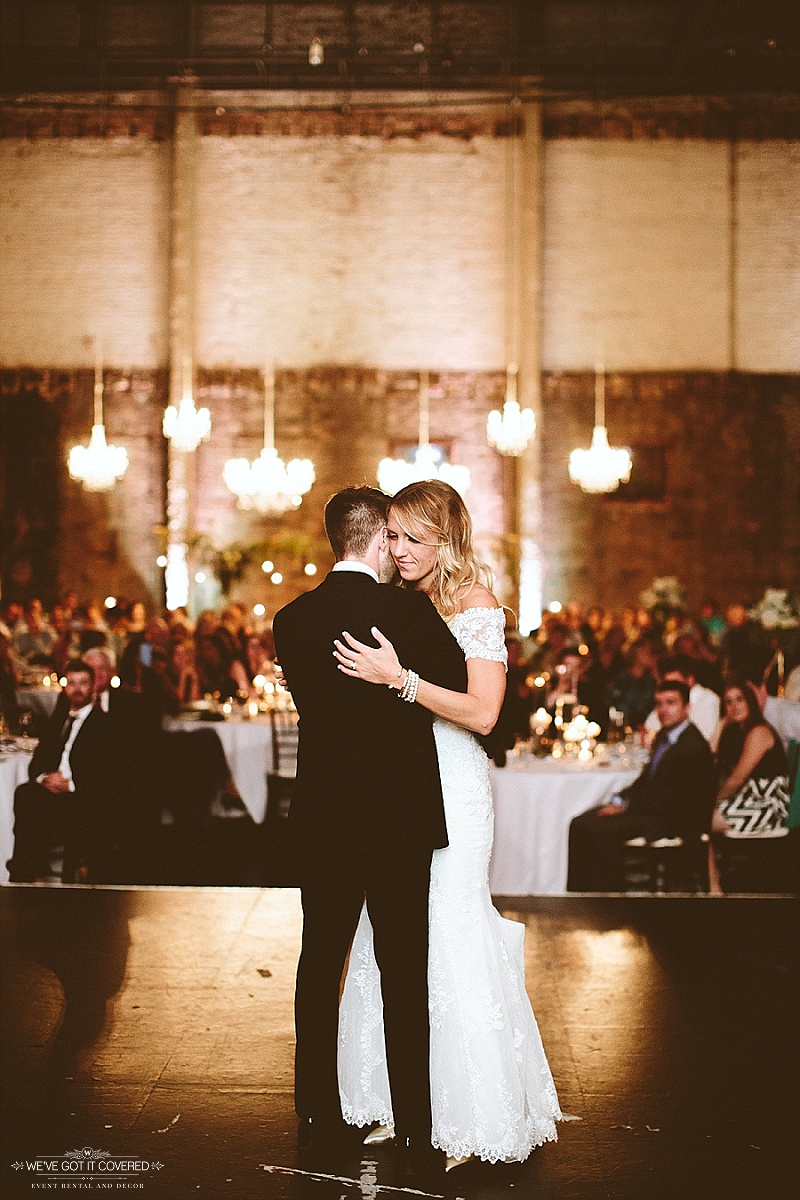 First dance as husband and wife on a stage with the glow of chandeliers and stunning decorations.