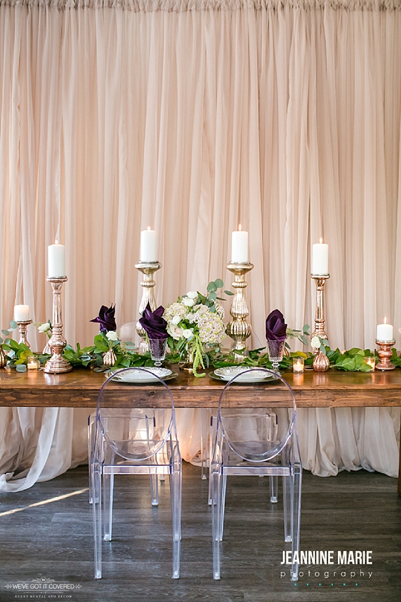 Farm table that has a beautiful taupe backdrop that make greenery and other decor stand out.