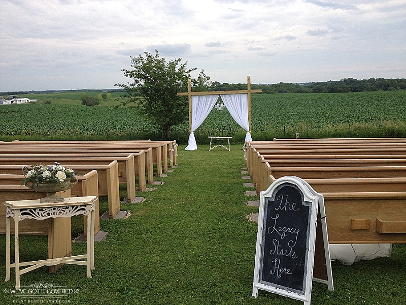 Added decor to an outdoor wedding site with chalkboard sign, antique tables and draping with a chandelier.