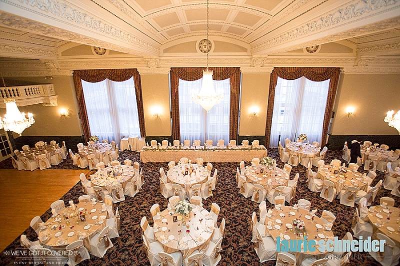 Birds eye view of wedding reception that has gold satin tablecloths and gold satin sashes