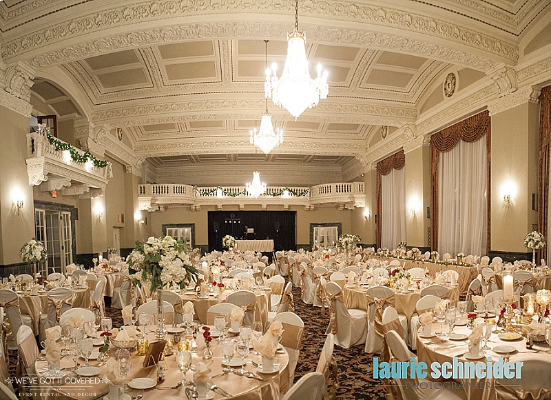 Wedding reception with gold sashes and table linens with chandeliers and balconys.