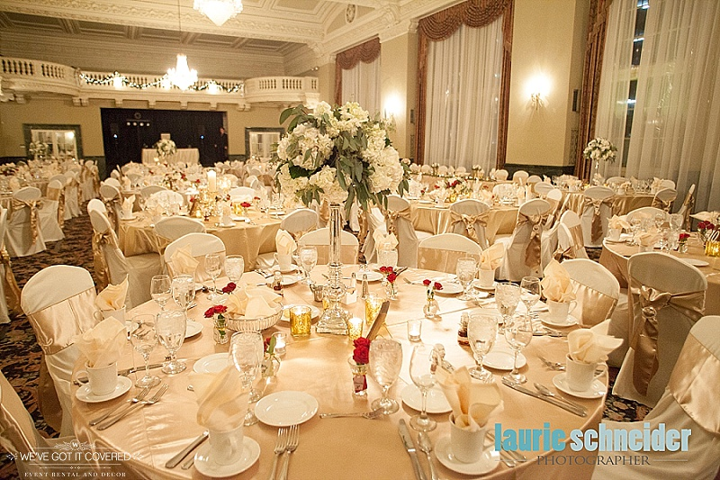 gold sashes with ivory chair covers and gold candle votives with white floral arrangements