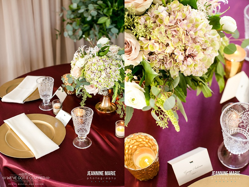 Burgundy linen with gold chargers, crystal cups, floral, and gold candle votive cups