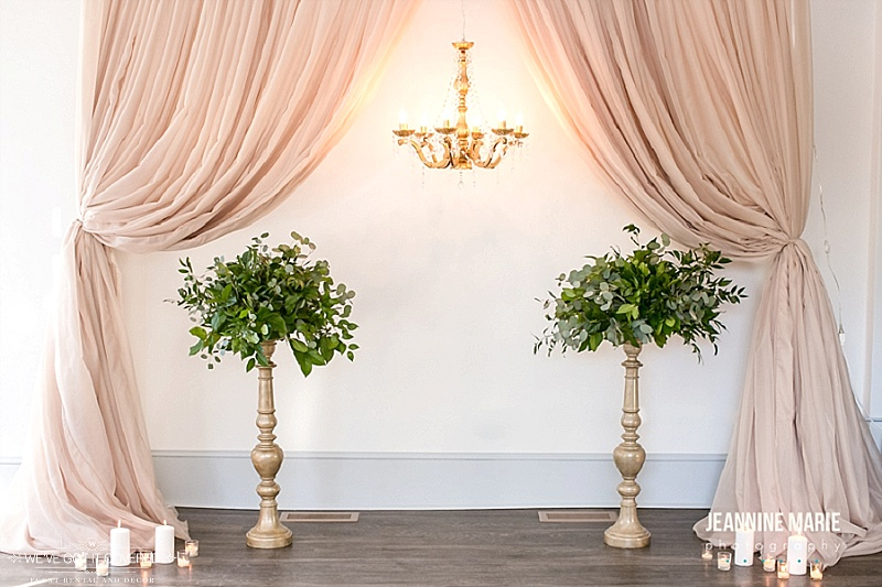 Taupe curtains pulled back with a gold chandelier and tall candlesticks holding eucalyptus