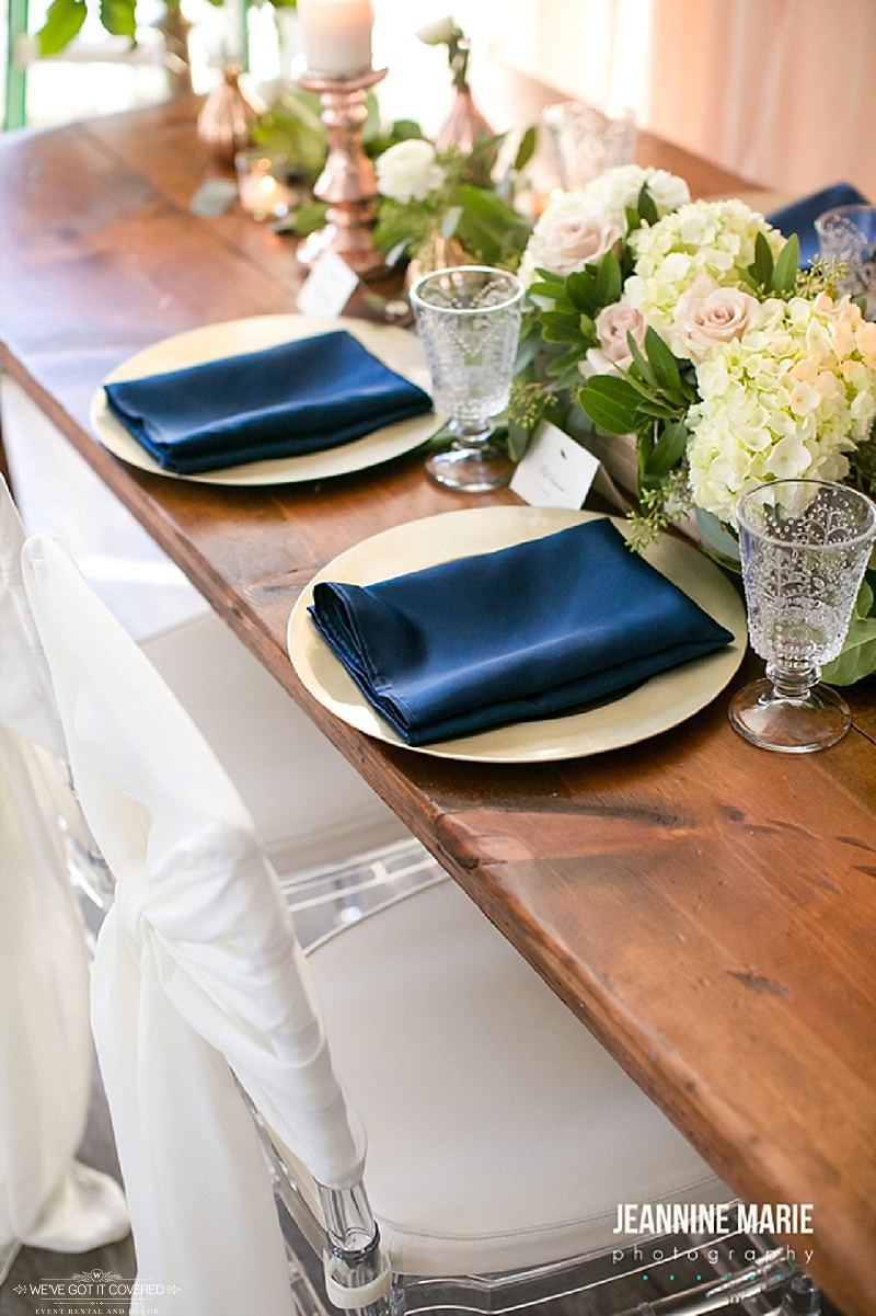 Navy and gold accent colors for wedding inspiration and crystal glasses on a farm table for extra glam