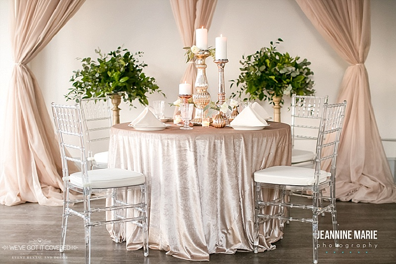 velvet linen on a wedding table with candlesticks for the centerpiece, taupe curtain backdrop, greenery, and chiavari chairs