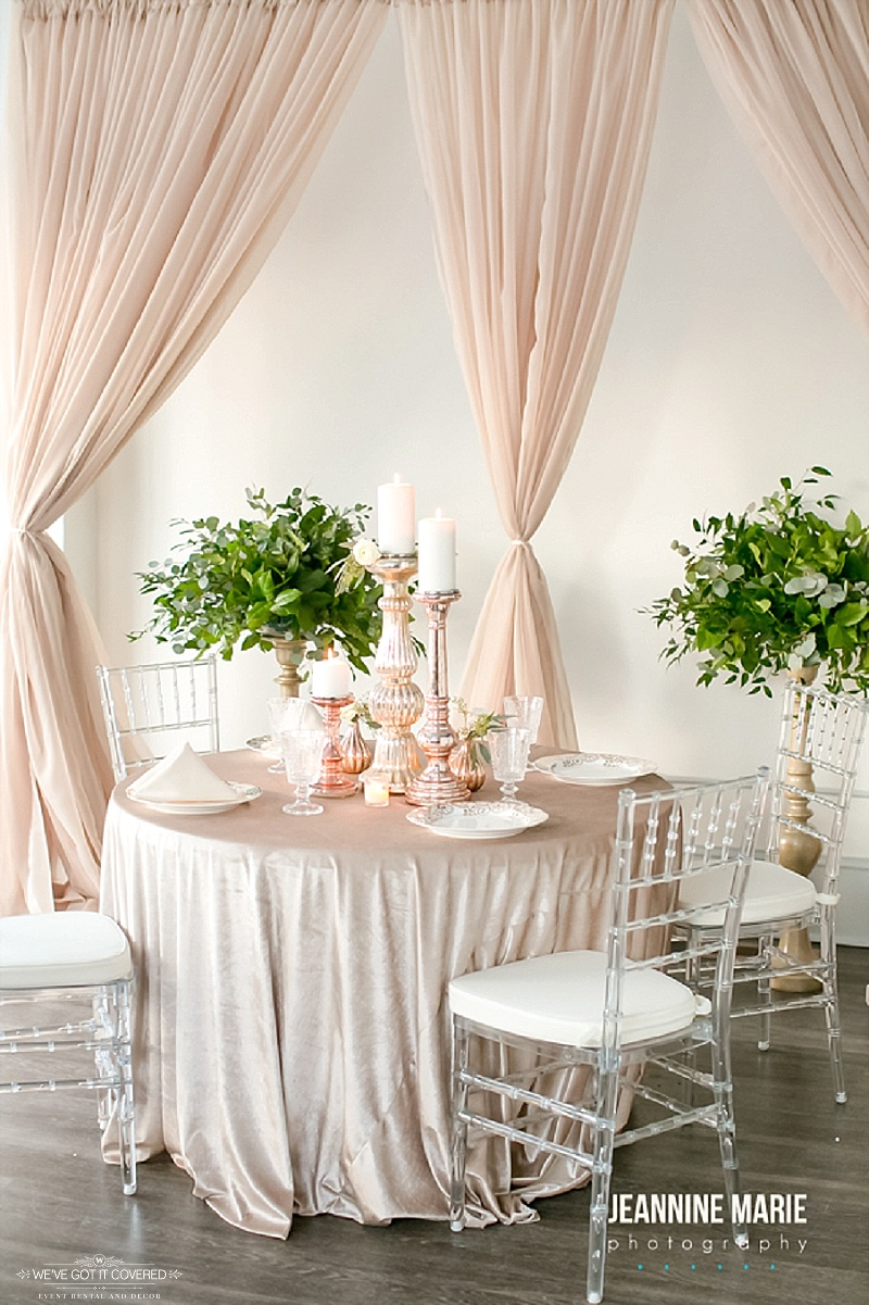 Different style backdrop behind wedding table and variety of centerpiece items like candlesticks, mercury bud vases, and unique plates and cups