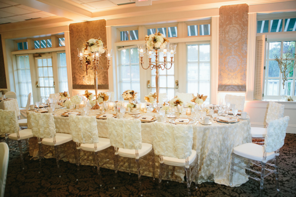 Rosette chair backs with rosette linen, candleabras holding candles and flowers with various flower displays for centerpieces