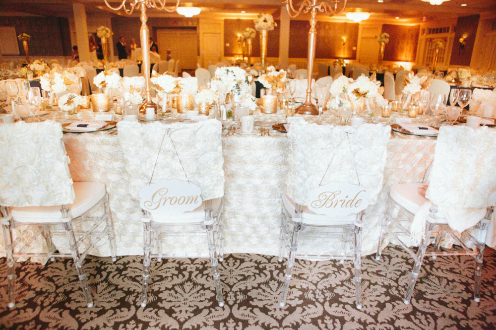 Bride and groom chairs with rosette flower linens and gold accents throughout