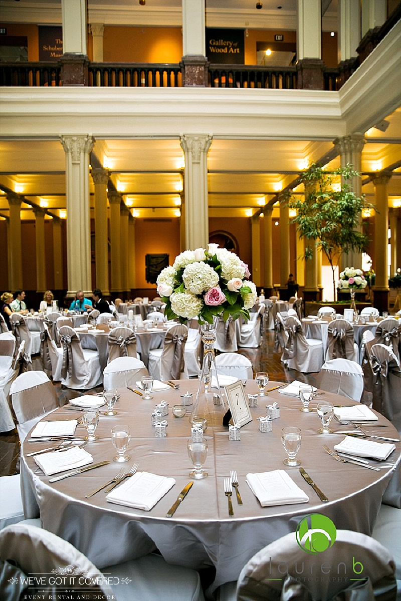 Silver satin table cloths with satin sashes and white chair covers styled at the landmark center