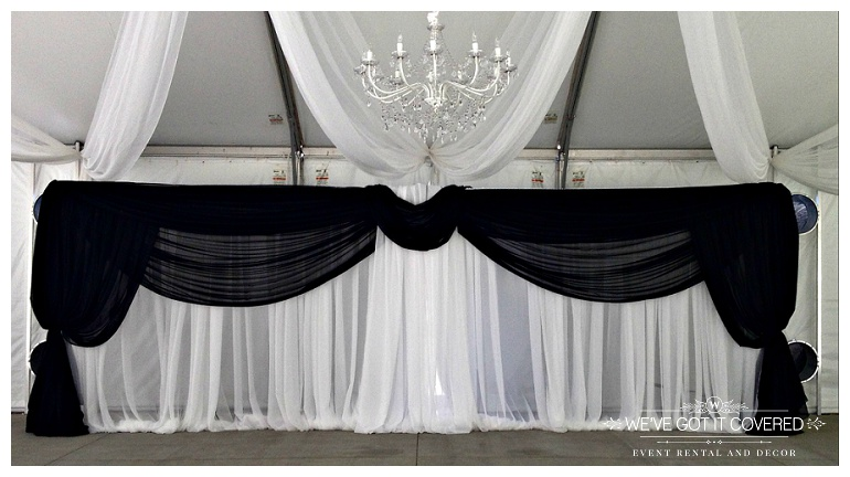 black draping hung on a backdrop inside a tent for a Minnesota wedding featuring a crystal chandelier