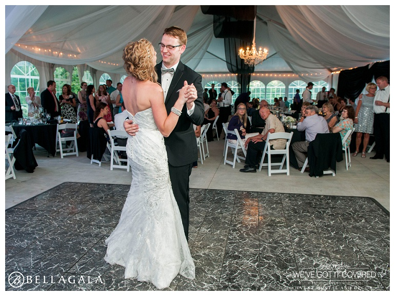 First dance as husband and wife inside a beautiful tent with chandelier lighting and black and white draping throughout