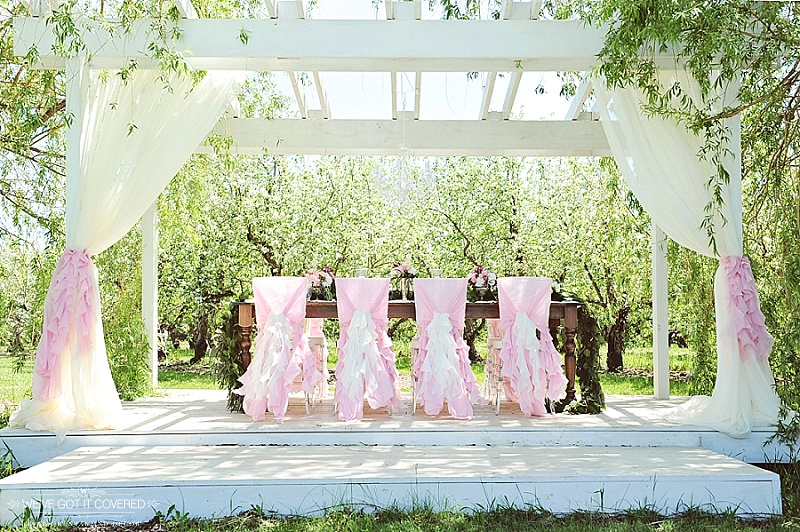 outdoor wedding arbor decorated with draping and pink accents on chairs and curtains
