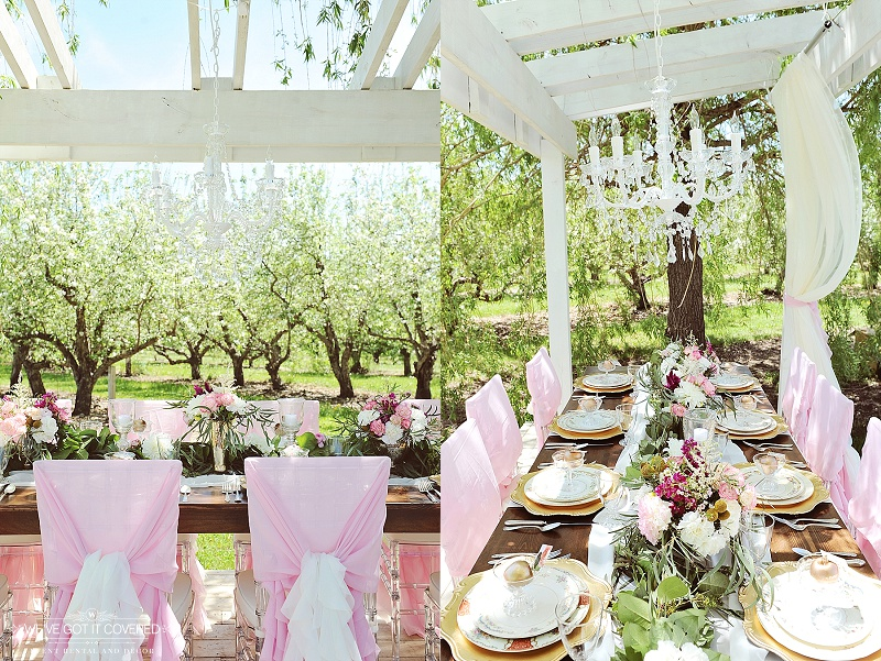 chandelier hung outside above a farm table decorated with colorful flowers, chargers and chiavari style chairs
