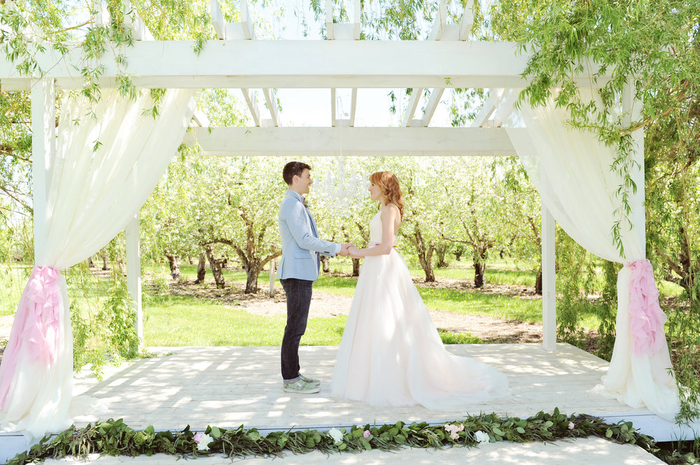 Spring style wedding using an outdoor arbor draped with curtains and pink ruffles