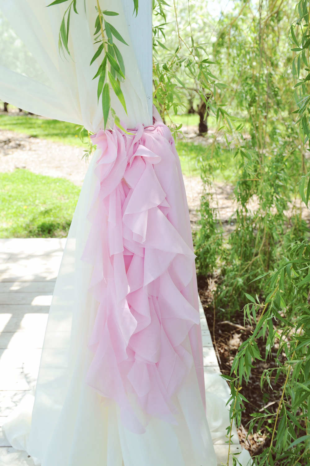 pink ruffles used for wedding day decorations tied in with ivory curtains for a soft and simple look