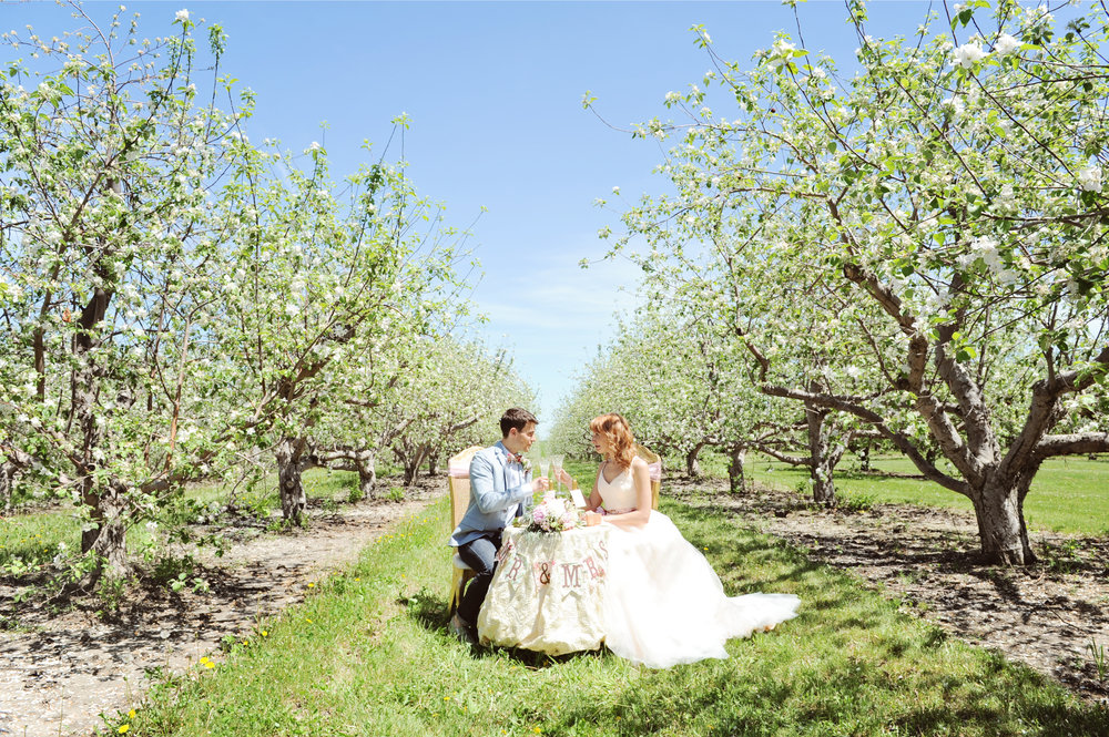 Husband and wife sharing meal at a sweetheart table in the middle of an apple orchard