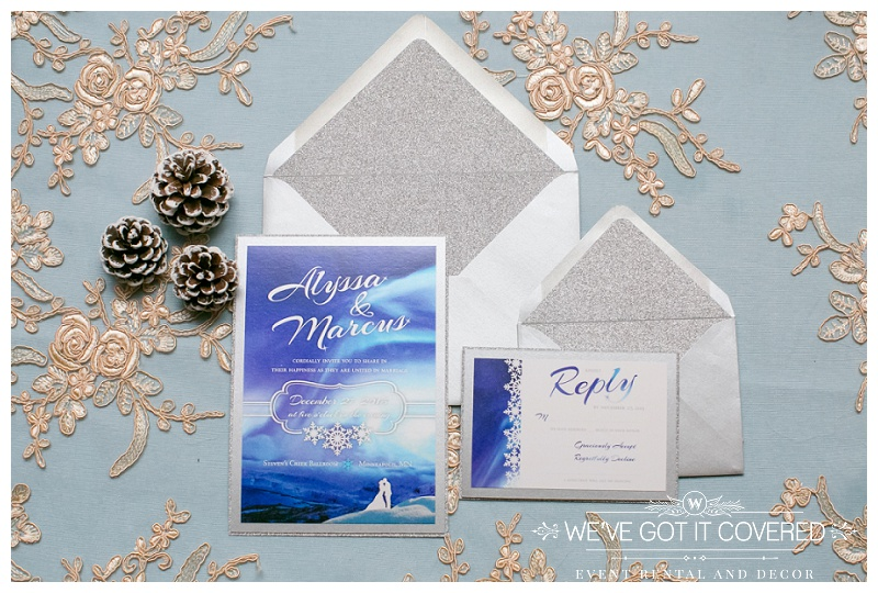 Wedding invitations displayed against blue table with lace linen and a few acorns for winter feels