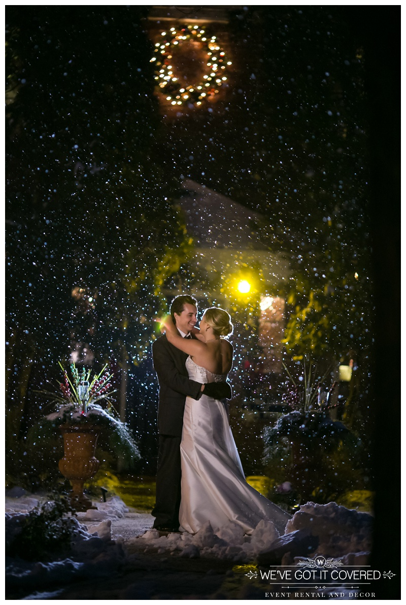 Outdoor snowfall wedding picture with berries and greens nearby.