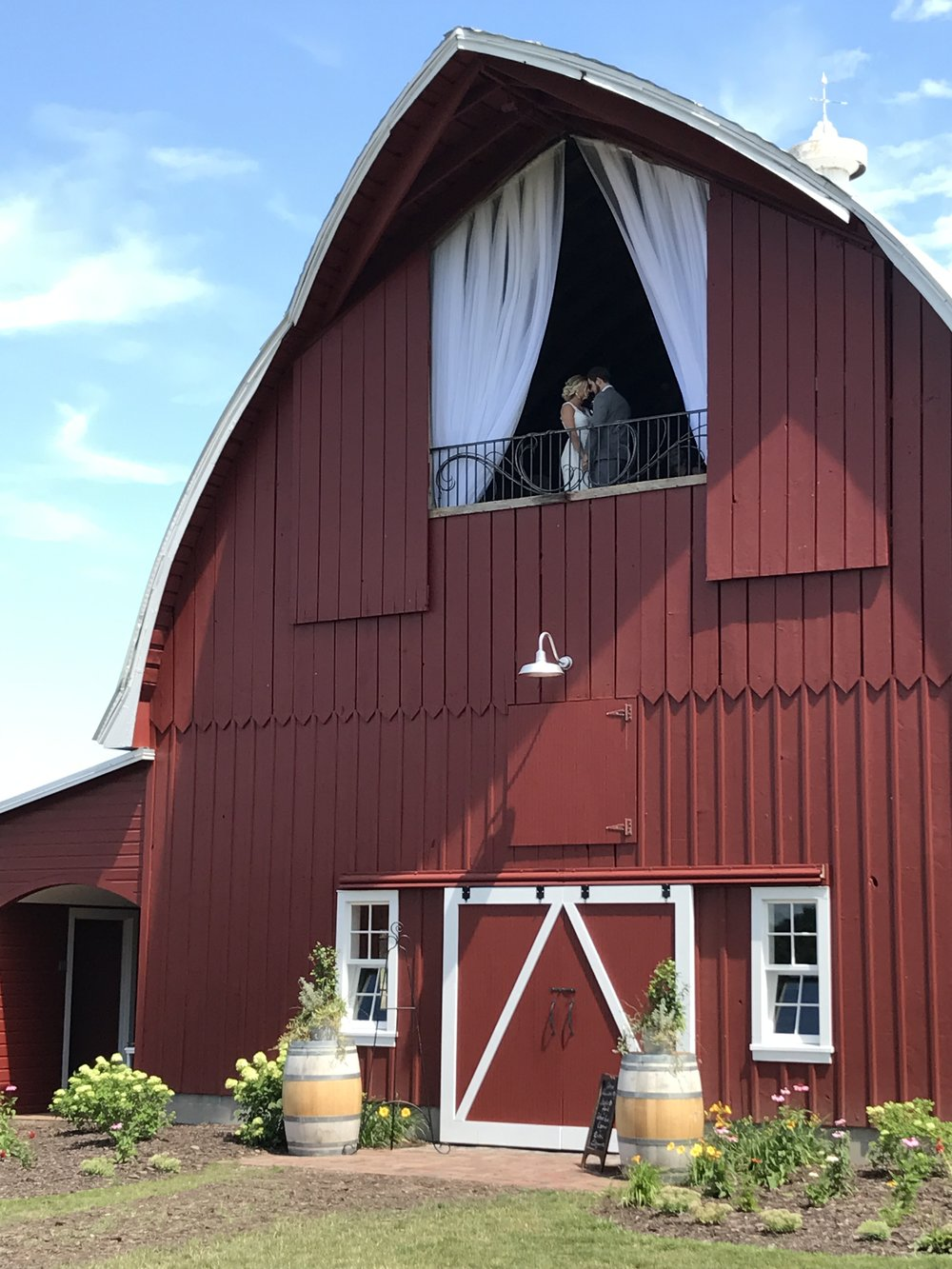 Dramatic draping hung in a classic red Minnesota barn for wedding ceremony / draping