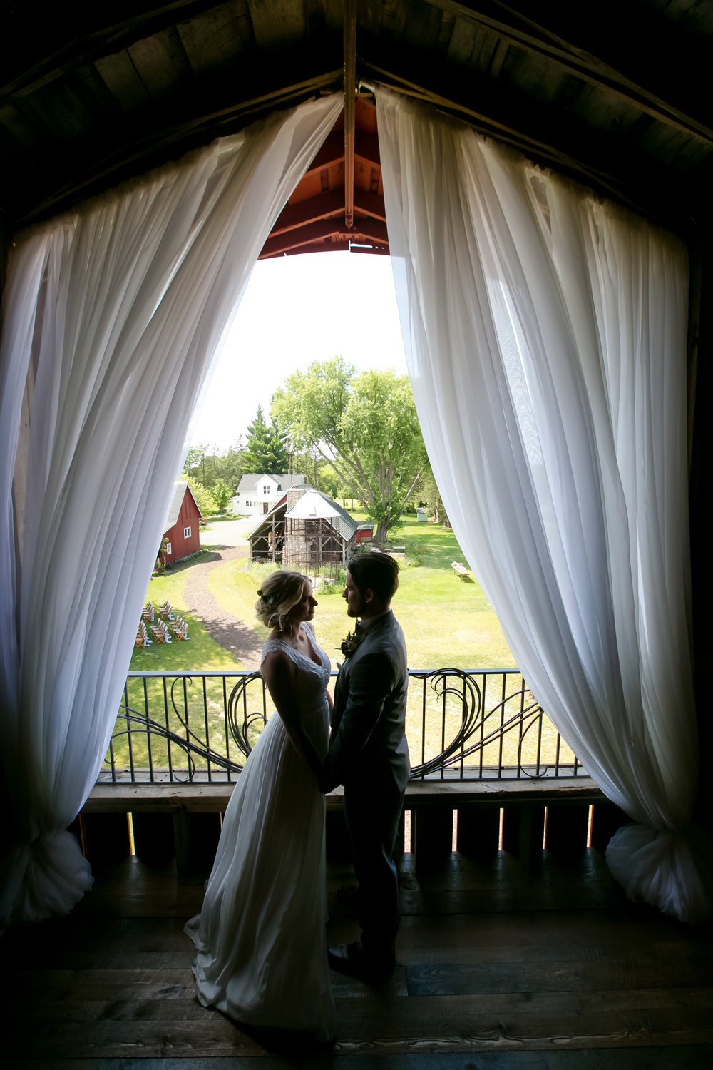 Wedding couple stands under beautiful draping on second story of a Minnesota barn venue / draping